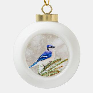 Arrendajo azul en un árbol de pino con nieve adorno de cerámica en forma de bola