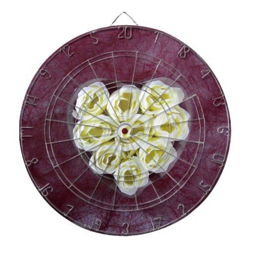 Artificial white cream flower on purple background dartboard with darts