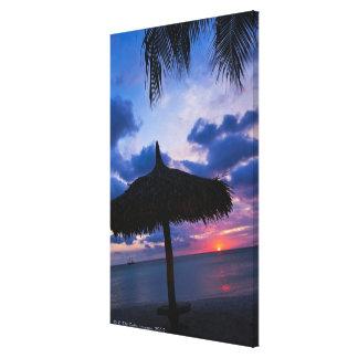 Aruba, silhouette of palapa on beach at sunset 2 canvas print