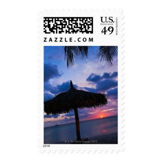Aruba, silhouette of palapa on beach at sunset 2 postage stamp