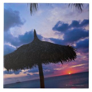 Aruba, silueta del palapa en la playa en la puesta azulejo cuadrado grande