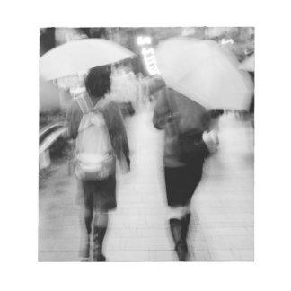 Asia, Japan, Tokyo. Young women and umbrellas. Notepad