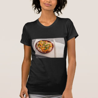 Asian dish of rice noodles in a small wooden bowl dresses