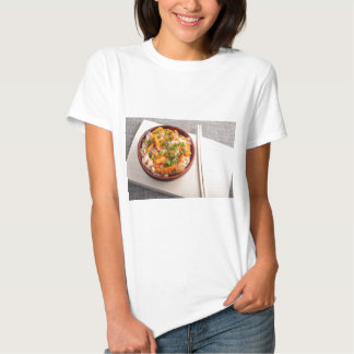 Asian dish of rice noodles in a small wooden bowl shirt
