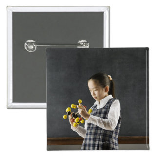Asian girl looking at molecule model 2 inch square button