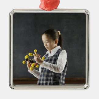 Asian girl looking at molecule model metal ornament