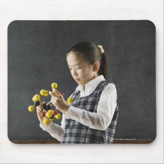 Asian girl looking at molecule model mouse pad