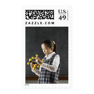 Asian girl looking at molecule model postage stamp