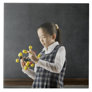 Asian girl looking at molecule model tile