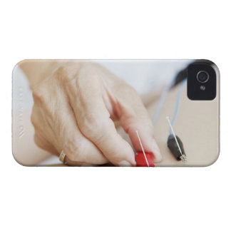 Asian woman (70-75 years old) putting red and iPhone 4 cover
