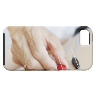 Asian woman (70-75 years old) putting red and iPhone SE/5/5s case