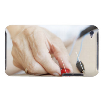 Asian woman (70-75 years old) putting red and iPod touch case