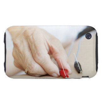 Asian woman (70-75 years old) putting red and tough iPhone 3 case