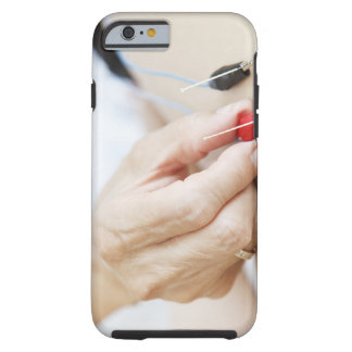 Asian woman (70-75 years old) putting red and tough iPhone 6 case