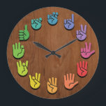"ASL Woodgrain Large Clock<br><div class=""desc"">ASL sign language hands clock,  with hands in color wheel colors,  on a woodgrain faux finish background.</div>"