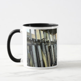 Assault rifles stand ready on the weapons rack mug