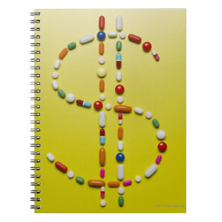 Assorted pills creating dollar symbol notebook