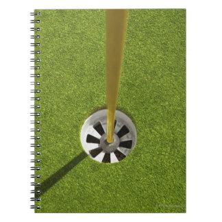 Asta de bandera y agujero amarillos del golf libreta espiral