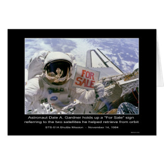 """Astronaut Dale A. Gardner holds up a """"For Sale"""" si Card"""