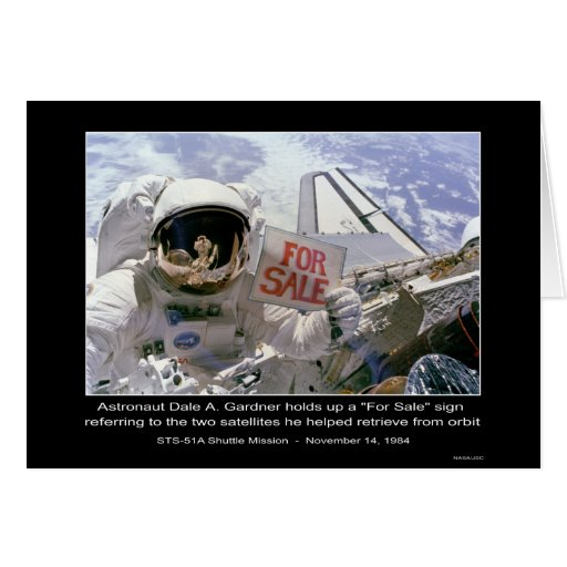 """Astronaut Dale A. Gardner holds up a """"For Sale"""" si Greeting Card"""
