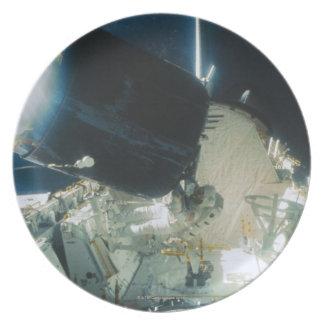 Astronautas que reparan un satélite en espacio platos