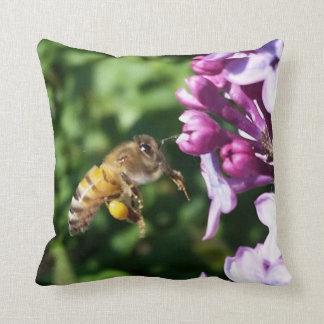 Aterrizaje de la abeja de la miel en las lilas cojín