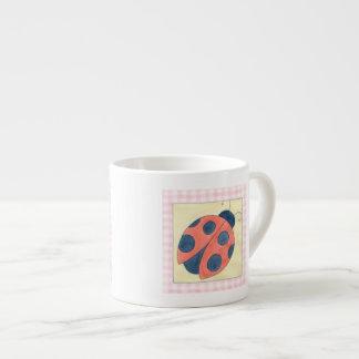 Aterrizaje del trío de la mariquita en las flores taza de espresso