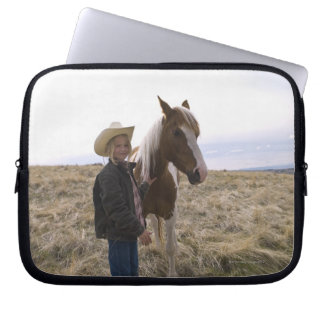 Authentic young cowgirl on range with horse in computer sleeve