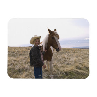 Authentic young cowgirl on range with horse in magnet