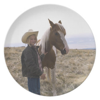 Authentic young cowgirl on range with horse in party plates