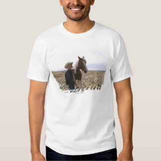 Authentic young cowgirl on range with horse in T-Shirt