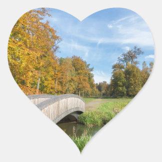Autumn forest landscape with wooden bridge over wa heart sticker