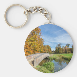 Autumn forest landscape with wooden bridge over wa keychain