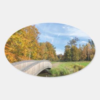 Autumn forest landscape with wooden bridge over wa oval sticker