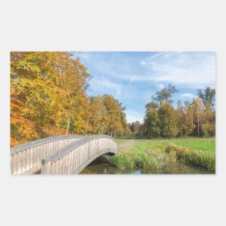 Autumn forest landscape with wooden bridge over wa rectangular sticker