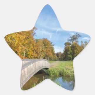 Autumn forest landscape with wooden bridge over wa star sticker