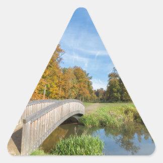 Autumn forest landscape with wooden bridge over wa triangle sticker