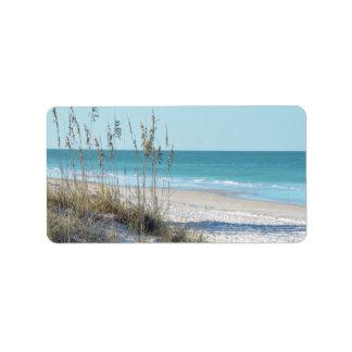 Avena serena del mar de la playa y agua azul etiqueta de dirección