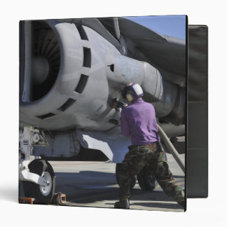 Aviation fuel technician attaches a fuel line 3 ring binders