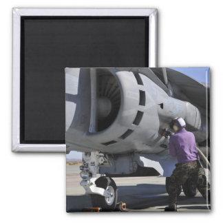 Aviation fuel technician attaches a fuel line magnet