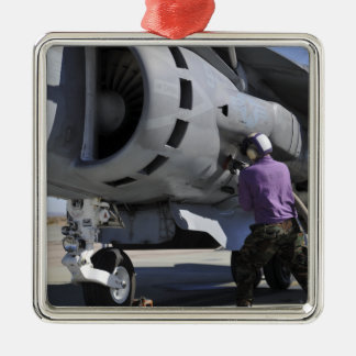 Aviation fuel technician attaches a fuel line metal ornament