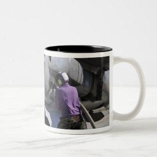 Aviation fuel technician attaches a fuel line coffee mug