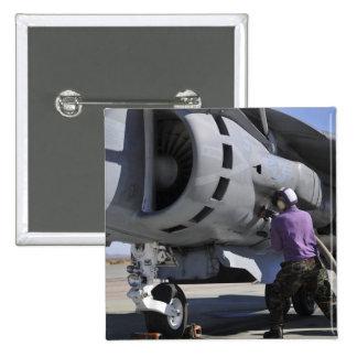 Aviation fuel technician attaches a fuel line pinback button