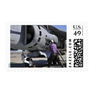 Aviation fuel technician attaches a fuel line postage