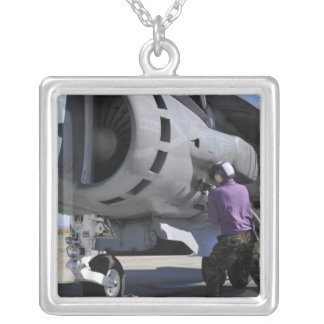 Aviation fuel technician attaches a fuel line silver plated necklace