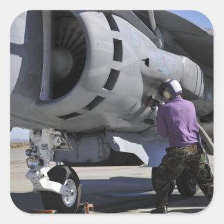 Aviation fuel technician attaches a fuel line square sticker