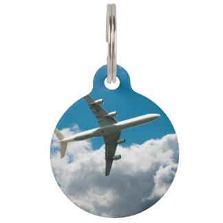 Avión de reacción que asciende en las nubes identificador para mascotas