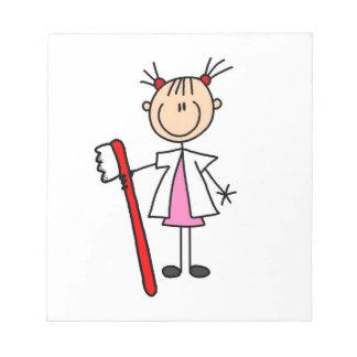 Ayudante de dentista con el cepillo de dientes bloc de notas