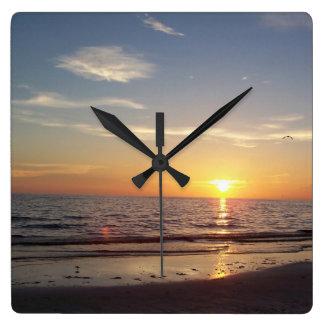azul y naranja de la puesta del sol de la playa reloj cuadrado