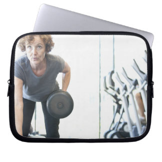 Baby boomer woman working out triceps in health computer sleeve